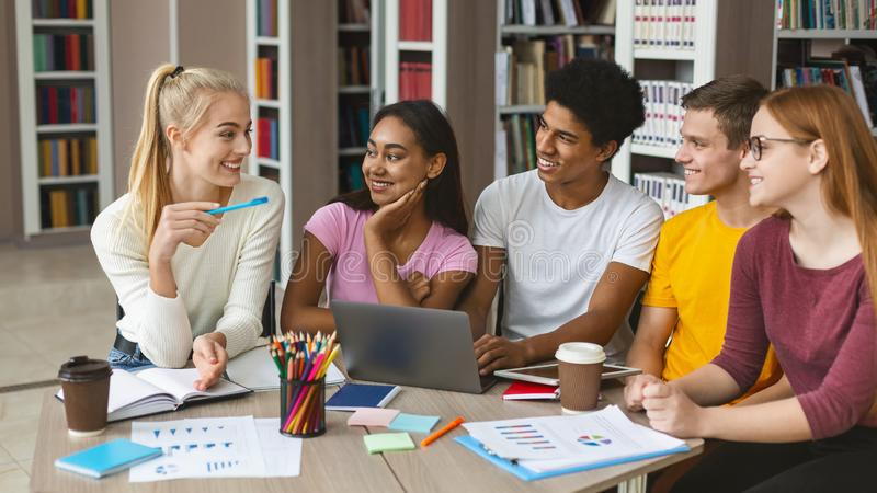 Blonde girl giving her opinion on research. Young caucasian girl expressing her opinion on research in front of group of international students, studying at royalty free stock photo
