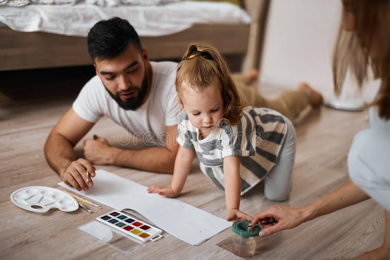 Blonde girl and her father looking at the cup with water, going to wet brush stock photos