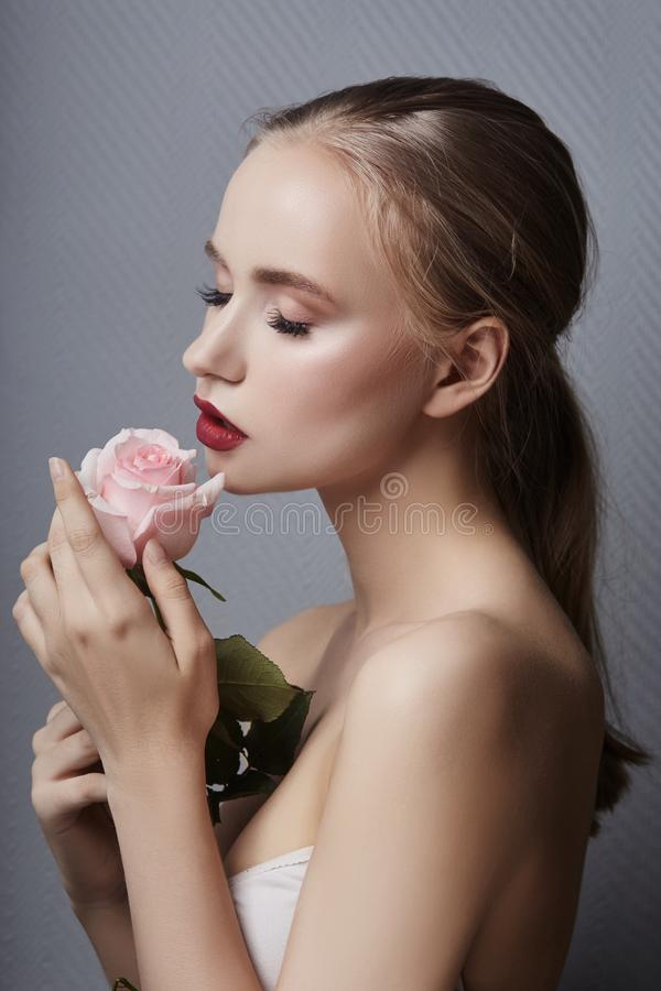 Free Blonde Girl Holding Rose Flowers Near Her Face. Beauty Portrait Of A Woman On A Dark Background. Perfect Makeup, Beautiful Body Royalty Free Stock Photos - 121911328