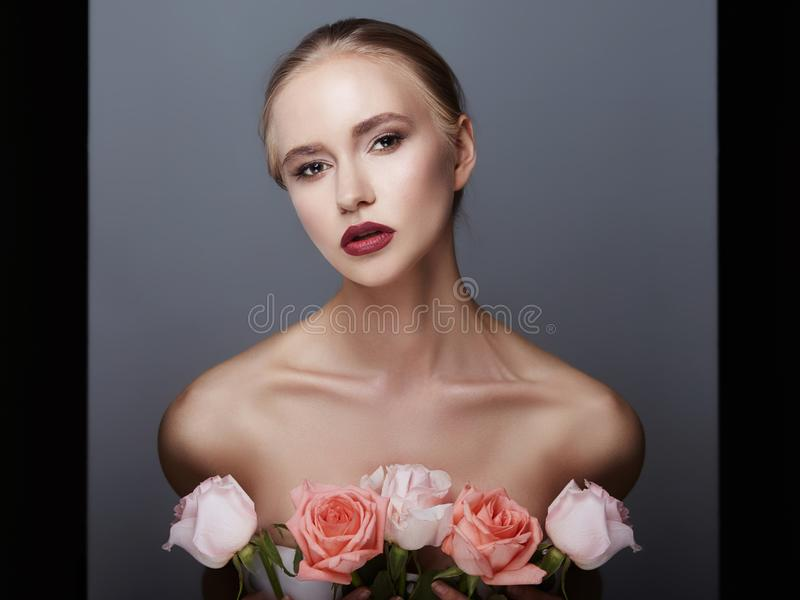Blonde girl holding rose flowers near her face. Beauty portrait of a woman on a dark background. Perfect makeup, beautiful body royalty free stock photo