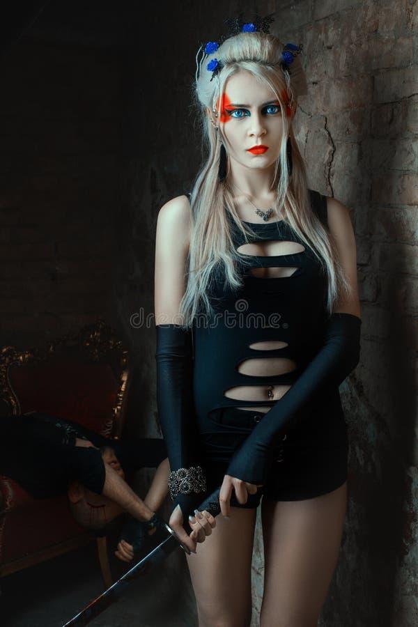 Blonde girl holding a samurai sword. Beautiful Girl killer stock photo