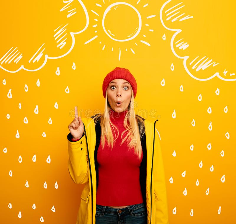 Girl indicates the sun between the clouds above. Amazed and shocked expression. Yellow background stock photography
