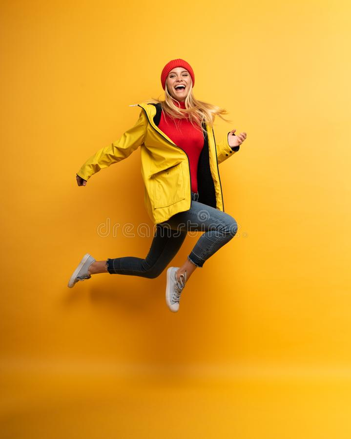 Girl with jacket jumps to the sun from the rainy weather. Joyful expression. Yellow background. Blonde Girl with jacket jumps to the sun from the rainy weather royalty free stock photo