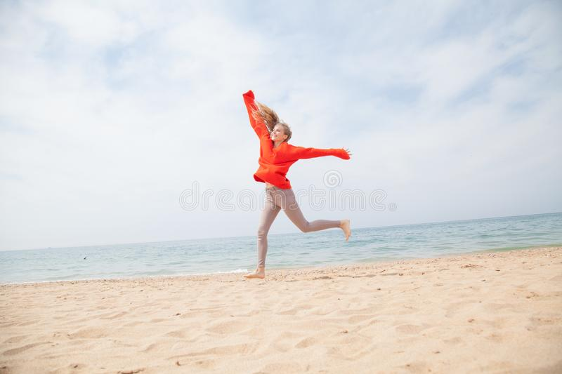 Blonde girl jumping on a sandy beach sea shore. 1 stock image