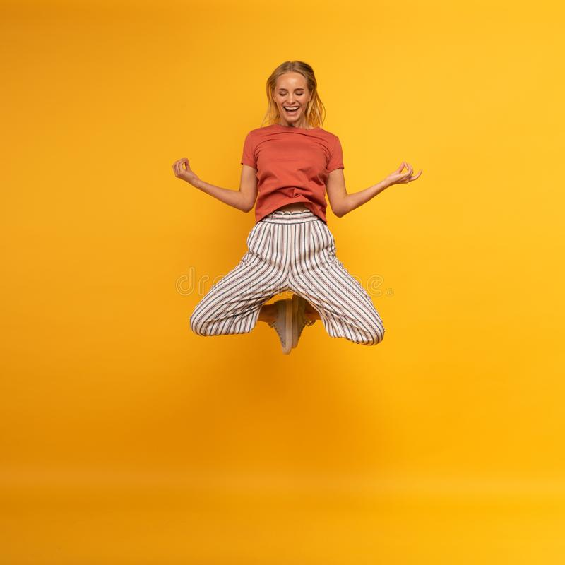 Blonde girl jumps in yogas position. Relax concept. Yellow background royalty free stock photography