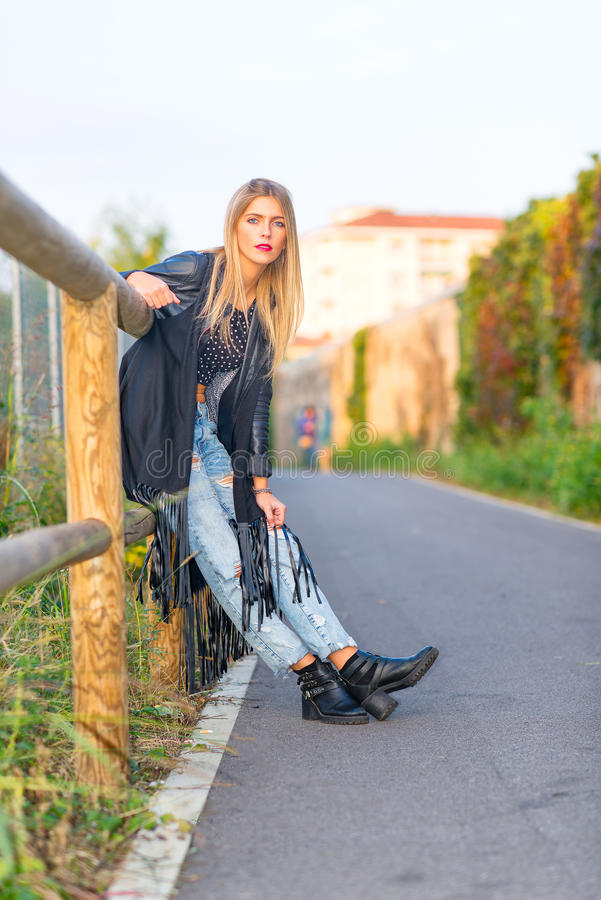 Blonde girl leaning on wooden fence stock images