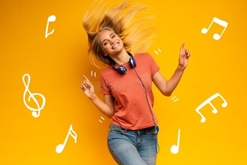 Blonde girl listens to music with headset. Joyful expression on yellow background stock photos