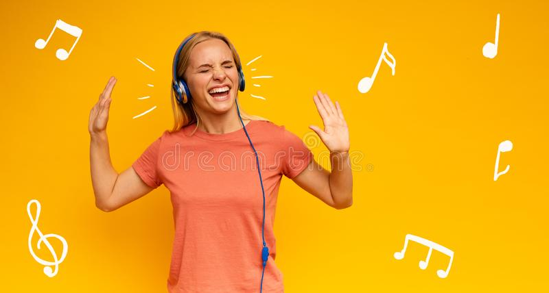 Blonde girl listens to music with headset. Joyful expression on yellow background stock images