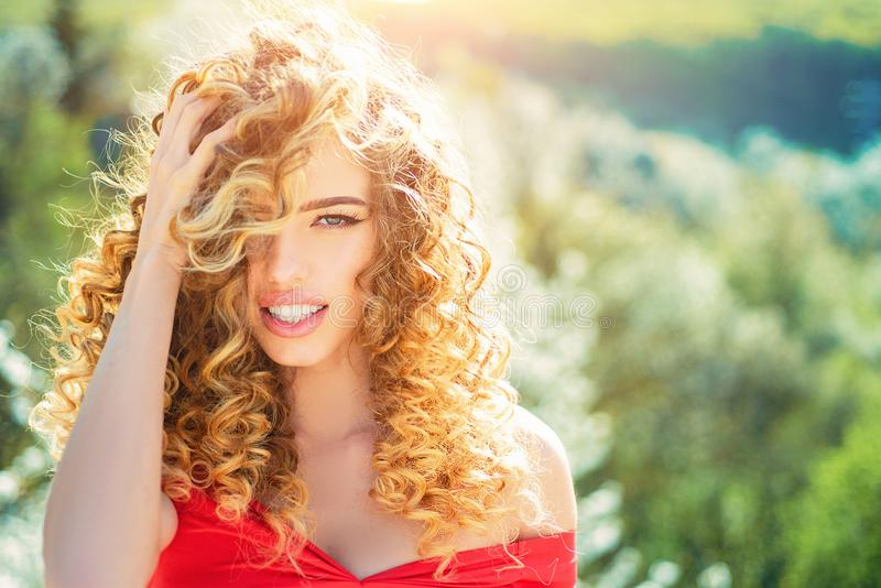 Blonde girl with long and curly wavy hair. Beautiful model with curly hairstyle. Fashion haircut. Beautiful attractive stock photo
