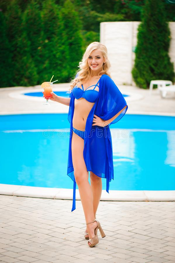Blonde girl with long hair holding cocktail and posing near pool on the sun stock images