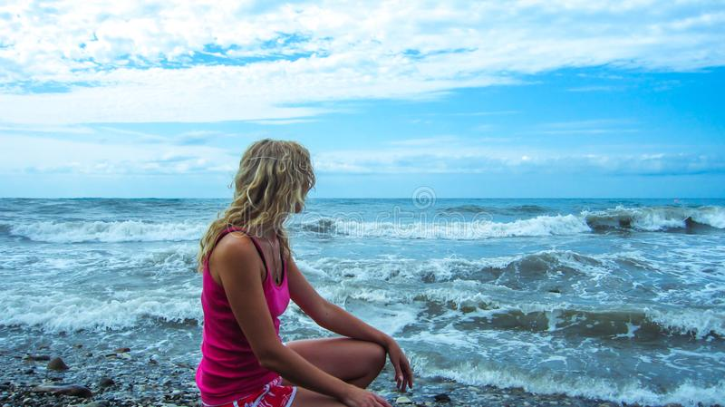 Blonde girl with long hair sits on the seashore stock photography