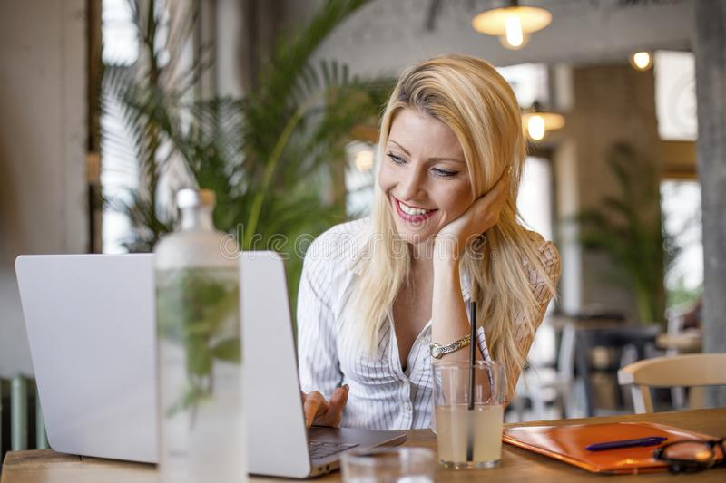 Blonde girl sitting in front of computer stock image