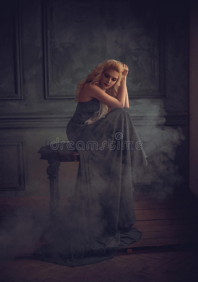 A blonde girl in a luxurious blue dress. With a long train. Gold make-up. Creative colors royalty free stock image