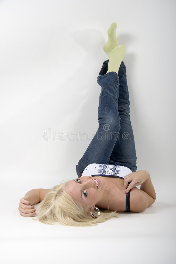 Blonde girl lying on her back. Blonde girl lying on white background legs in air royalty free stock images