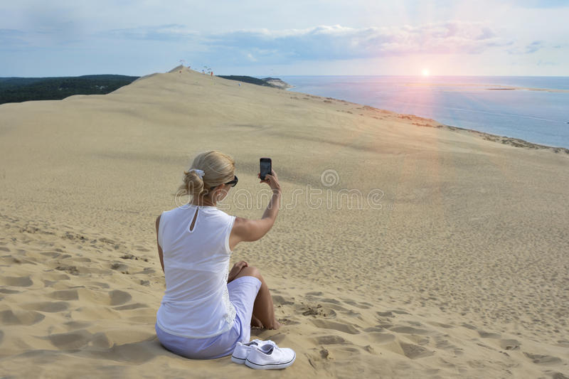 Blonde girl making selfie for instagram at Pyla dune, the largest sand dune in Europe stock images