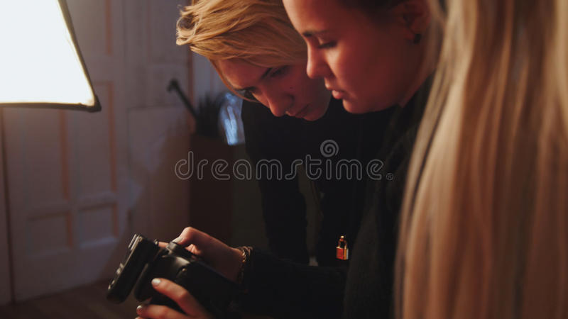 Blonde girl model and photographer in photo studio watching photos in camera, fashion backstage. Horizontal stock photography