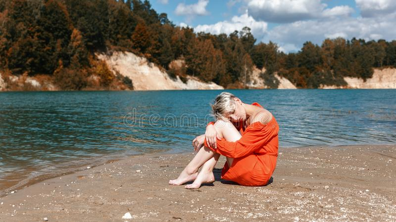 Blonde girl sits on the beach near the blue sea. Blonde girl in orange dress walking on sandy beach stock photography