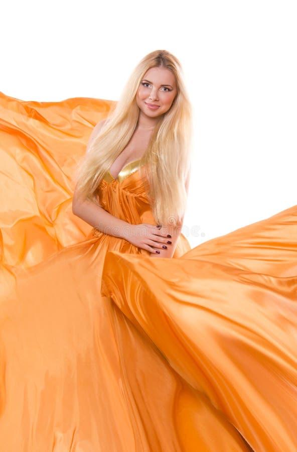Blonde girl in orange flying dress stock photos