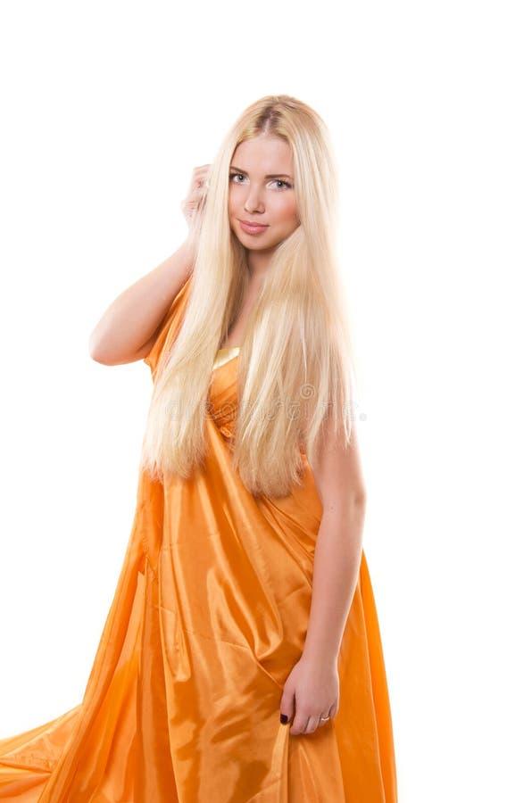 Blonde girl in orange flying dress stock photo