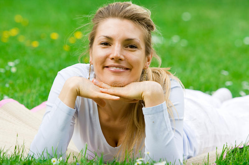 Blonde girl in park relaxing. Blonde girl in nature green park relaxing and chilling out stock photos