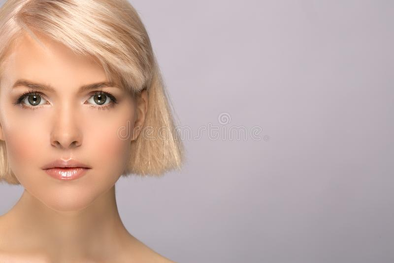 Blonde girl portrait. Blonde girl with perfect skin and short haircut looking at camera, studio portrait on gray background with copy space royalty free stock photo
