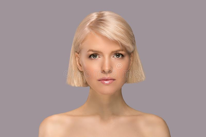 Blonde girl portrait. Blonde girl with perfect skin and short haircut looking at camera, studio portrait on gray background stock image