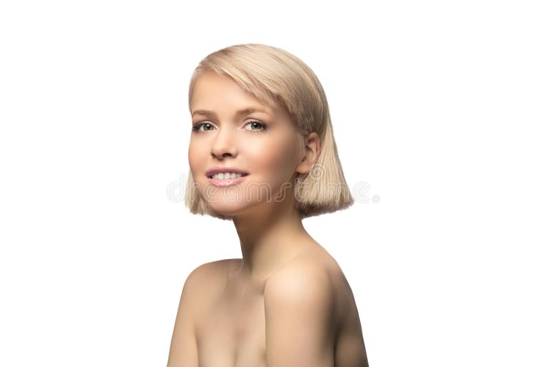 Blonde girl portrait. Blonde girl with perfect skin and short haircut looking at camera, studio portrait isolated on white background royalty free stock photo