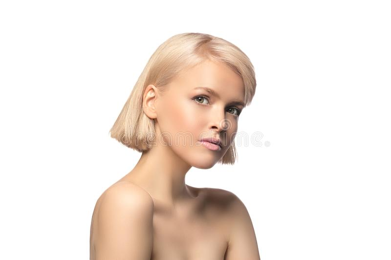 Blonde girl portrait. Blonde girl with perfect skin and short haircut looking at camera, studio portrait isolated on white background stock photography
