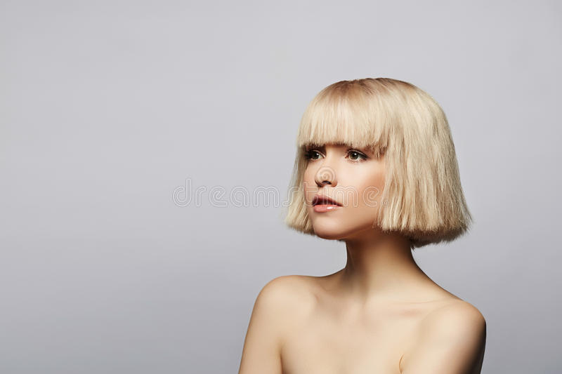 Blonde girl portrait. Blonde girl with perfect skin and short haircut looking aside, studio portrait on gray background with copy space stock photos