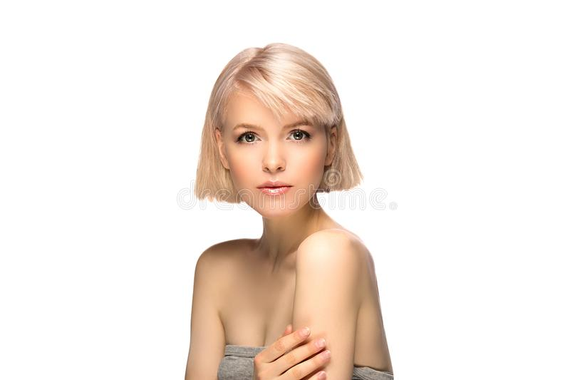 Blonde girl portrait. Blonde girl with perfect skin and short haircut looking at camera, studio portrait isolated on white background stock image