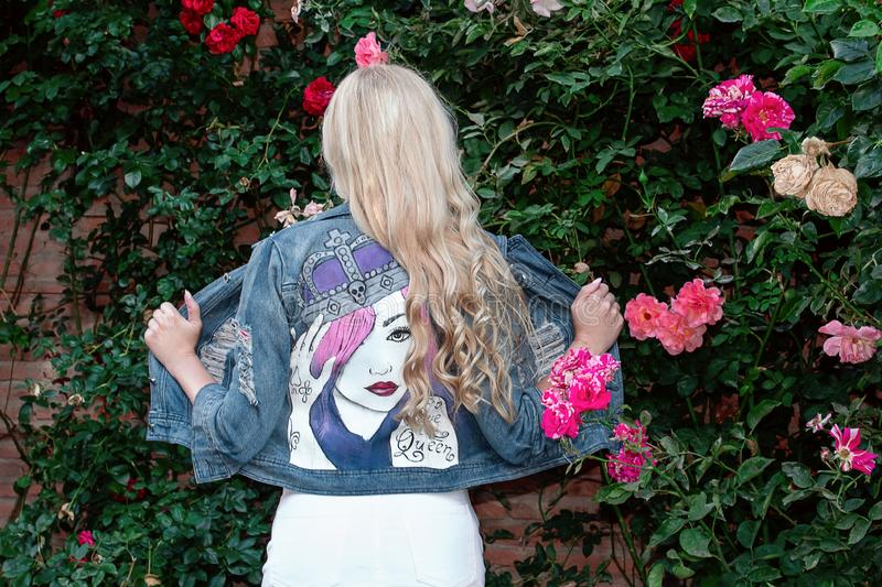 Blonde girl posing in a painted Jean jacket on a background of greenery and flowers. stock photography