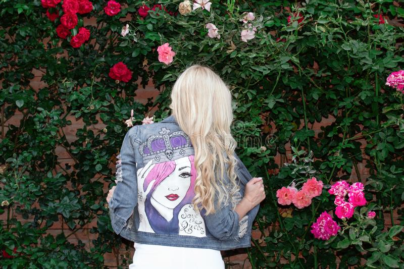 Blonde girl posing in a painted Jean jacket on a background of greenery and flowers. royalty free stock images