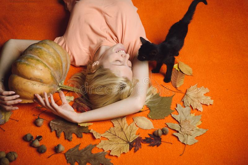 Blonde girl with Pumpkin and black cat. Halloween party. Halloween wide poster for Happy halloween celebrate. Cheerful. Woman with pumpkin over orange stock photo