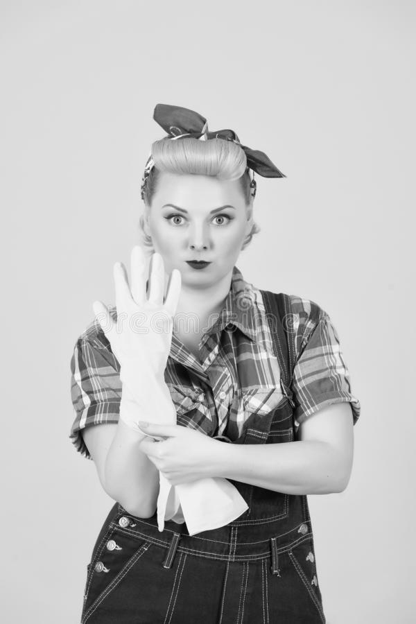 Blonde girl is ready to clean. pin up styled blonde girl take on hand gloves royalty free stock photography