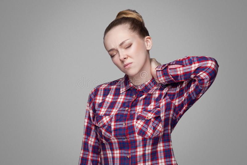 Blonde girl in red, pink checkered shirt, collected bun hairstyle, makeup standing with closed eyes and touching her painful neck royalty free stock photos
