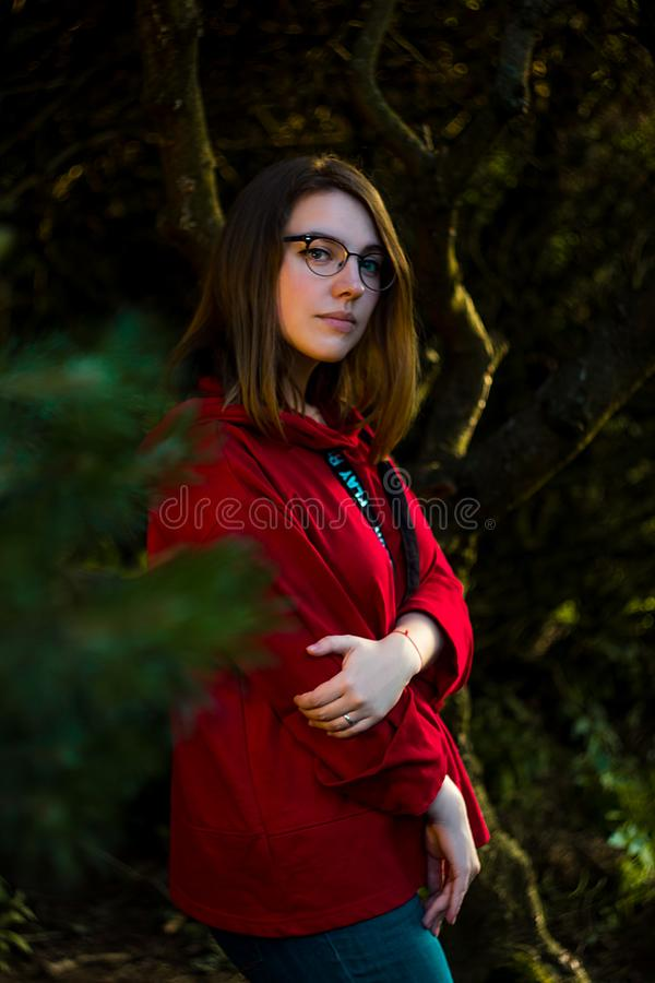 Blonde girl in red sweatshirt and glasses stock image
