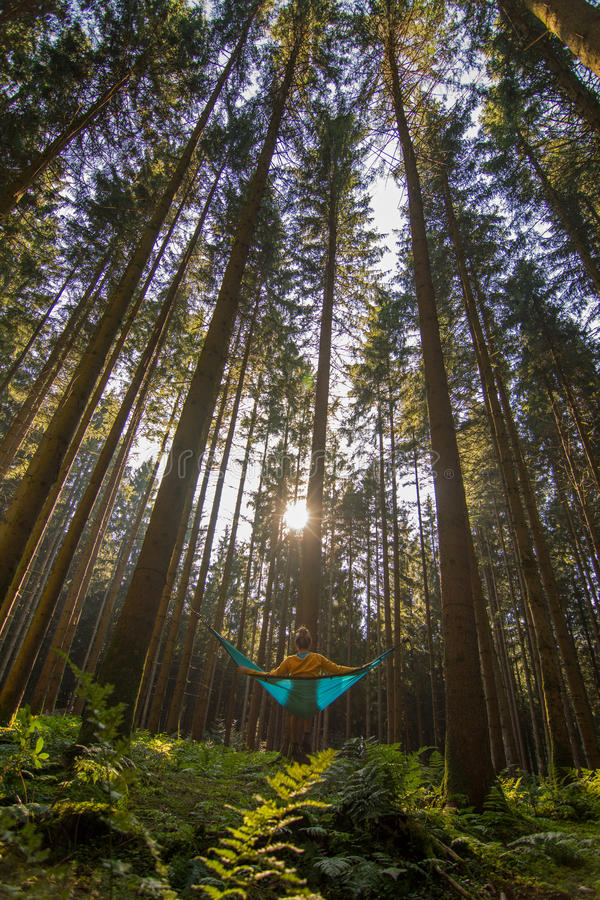 Blonde girl relaxing in blue hammock into the forest Beautiful destination form Germany for relaxing and spending quality time in stock image