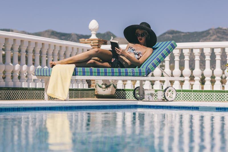 Blonde girl relaxing poolside reading stock image