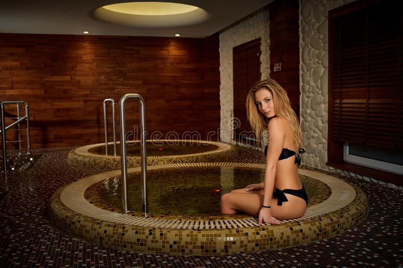 Girl resting in a jacuzzi in a spa center. royalty free stock images