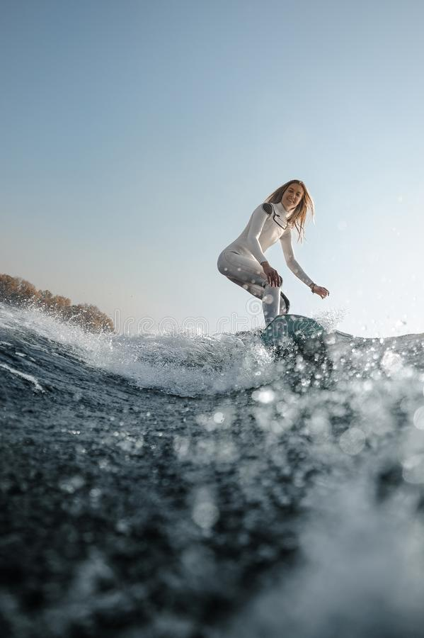 Blonde girl riding on the wakeboard on the river stock photos