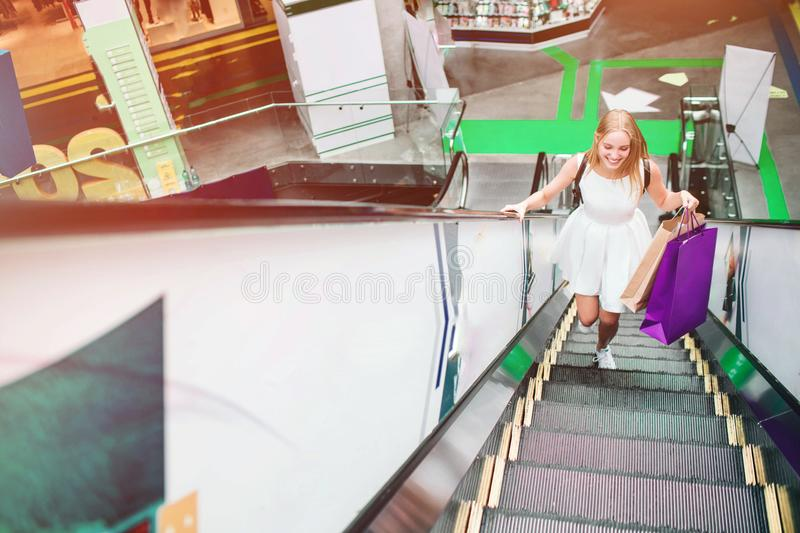 Blonde girl is running up on escalator. She has violet bags in her left hand. She is in a rush. stock photos