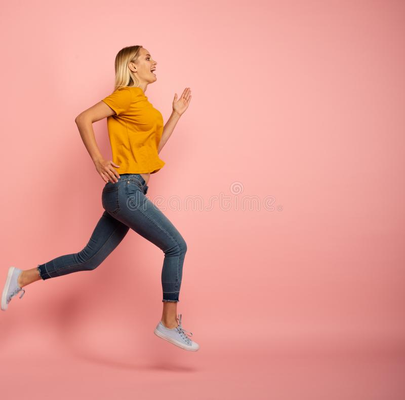 Girl runs fast. Concept of energy and vitality. Pink background stock photo