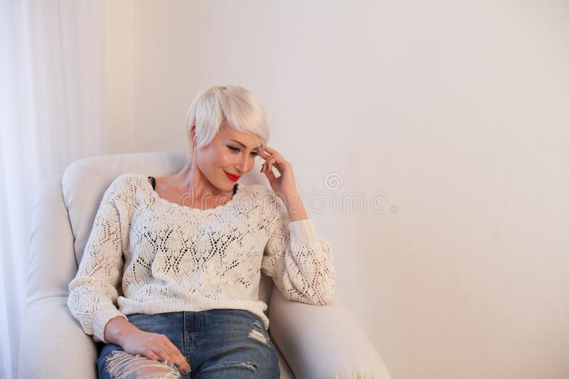 Blonde girl with short hair sits in a white armchair royalty free stock image