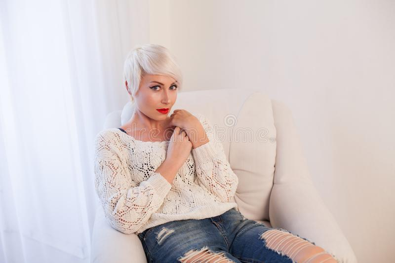 Blonde girl with short hair sits in a white armchair royalty free stock images