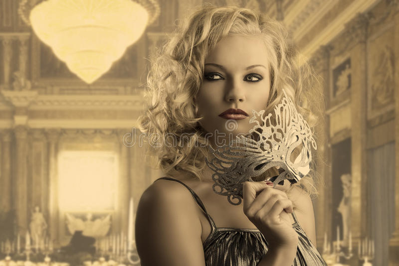 Blonde girl with silver mask looks at right stock photos