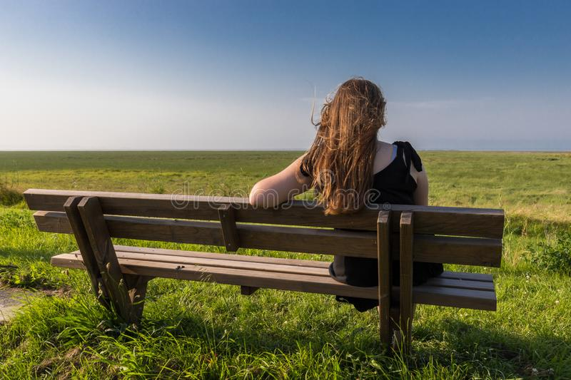 Blonde girl sitting on a bench royalty free stock photo
