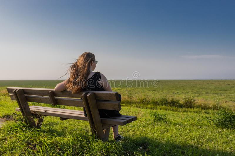 Blonde girl sitting on a bench stock photos