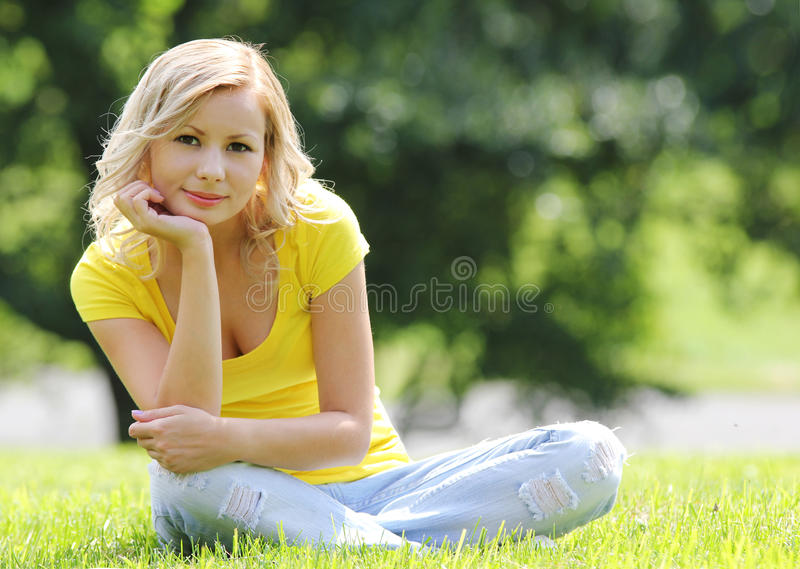 Blonde girl sitting on the grass and smiling. Looking at the camera. Outdoor. Sunny day. stock photo
