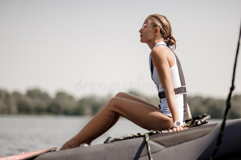 Blonde girl sitting near the lake on the pier royalty free stock photography