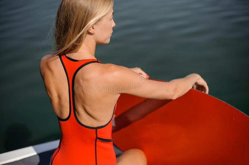 Blonde girl sitting near the lake with a red wakeboard. Beautiful blonde girl in the red swimsuit sitting near the lake with a red wakeboard stock image
